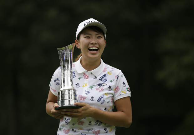 Japan's Hinako Shibuno reacts as she holds the trophy as she celebrates after winning the Women's British Open golf championship at Woburn Gold Club near near Milton Keynes, England, Sunday, Aug. 4, 2019. (AP Photo/Tim Ireland)