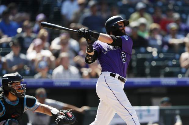 Colorado Rockies' Charlie Blackmon, right, follows the flight of his solo home run off Miami Marlins starting pitcher Jordan Yamamoto in the sixth inning of a baseball game Sunday, Aug. 18, 2019, in Denver. (AP Photo/David Zalubowski)