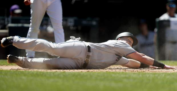Miami Marlins' Garrett Cooper holds onto home plate after scoring on a single hit by Harold Ramirez off Colorado Rockies starting pitcher Peter Lambert in the fourth inning of a baseball game Sunday, Aug. 18, 2019, in Denver. (AP Photo/David Zalubowski)