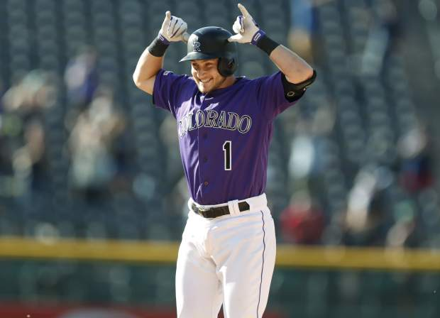 Colorado Rockies' Garrett Hampson celebrates after his walkoff RBI-single off Miami Marlins relief pitcher Jeff Brigham in the 10th inning of a baseball game Sunday, Aug. 18, 2019, in Denver. (AP Photo/David Zalubowski)