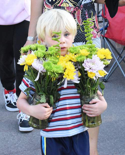 Kade Mason carries flowers through the crowd on Carbondale's Fourth Street Sunday to help decorate a table for the Our Town, One Table community picnic.