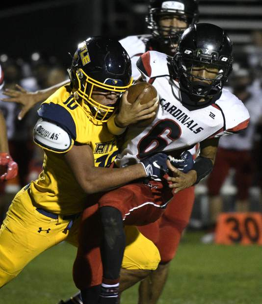 Rifle's Tyler Vasquez wraps up Grand Valley quarterback Hector DeLaCruz in the third quarter. The Bears took down the Cardinals 47-7 Friday in Rifle.