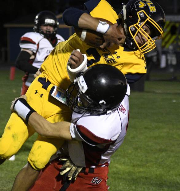 Rifle's Kenny Tlaxcala leaps over Grand Valley's Steven Hicks for the touchdown during secodn quarter action Friday in Rifle. The Bears defeated the Cardinals 47-7 in their season opener.
