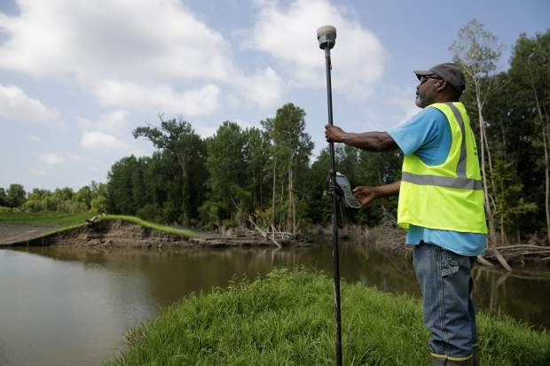 In this photo taken Tuesday, Aug. 6, 2019, U.S. Army Corps of Engineers worker Ron Allen uses a GPS tool to survey the extent of damage where a levee failed along the Missouri River near Saline City, Mo. The Corps of Engineers estimates it will cost $1 billion to repair flood damaged levees in the Missouri River basin alone.(AP Photo/Charlie Riedel)