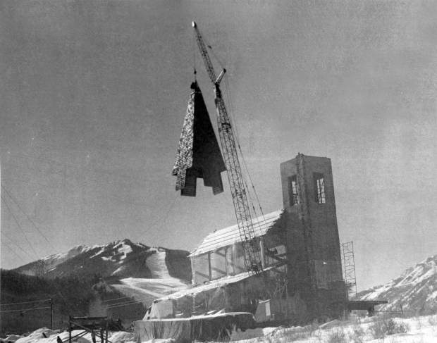 The Aspen Chapel's 40-foot-high steeple hangs from a crane before it is placed on the tower in December 1968.