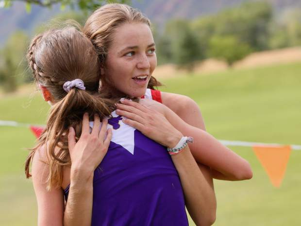 Glenwood Springs High School freshman Sophia Connerton-Nevin, back in red, hugs Basalt junior Sierra Bower after completing the Longhorn Invitational on Saturday, Aug. 24, 2019, at Crown Mountain Park. Bower finished first and Connerton-Nevin second in the season-opening girls cross country race, hosted by Basalt. The Longhorns will also host the regional meet at Crown Mountain Park later in the season. (Photo by Austin Colbert/The Aspen Times)