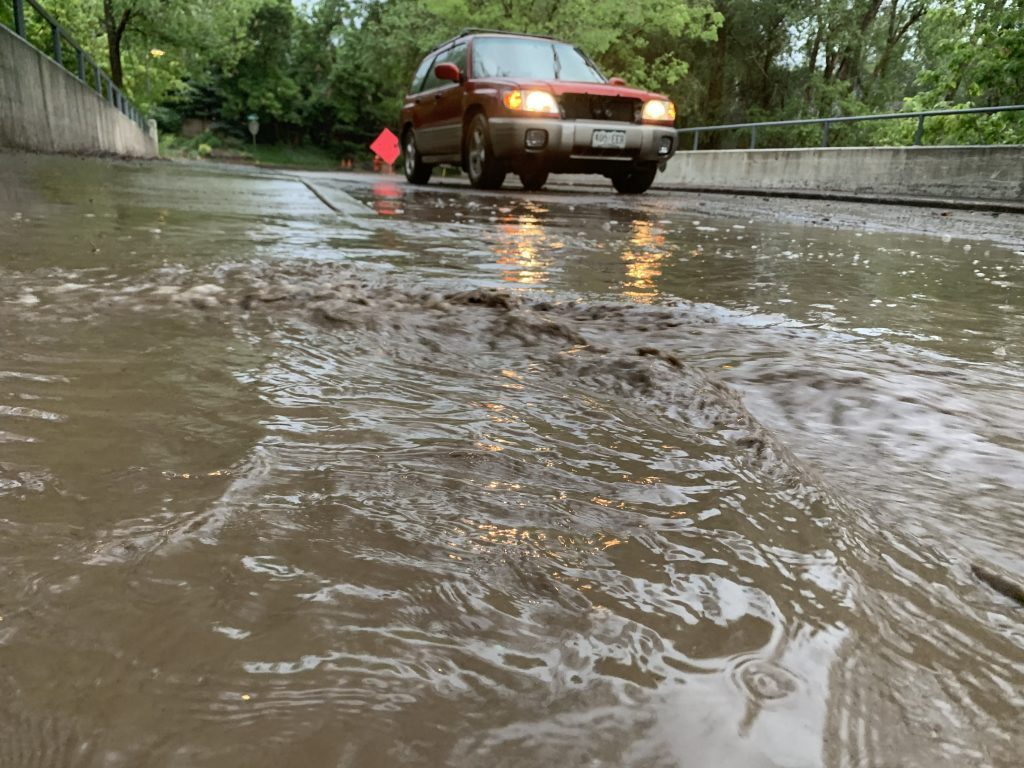 A car makes its way down Riverside Drive in Basalt Sunday evening after flooding from heavy rains.