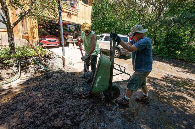 Patrick Seurynck, right, helps his neighbor Doug McLaughlin clear mud from his driveway on Sopris Drive in Basalt on Monday after the flash flooding from the rainstorm Sunday night.