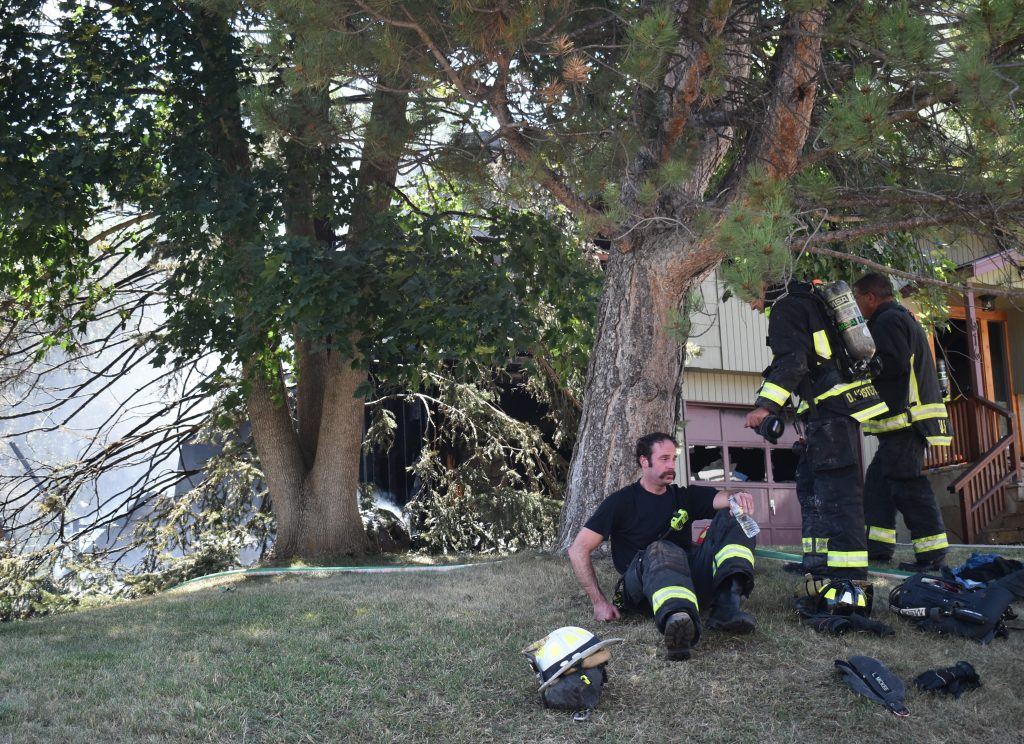 Firefighters take a short break while working to extinguish a house fire in Glenwood Springs Tuesday, Aug. 21.