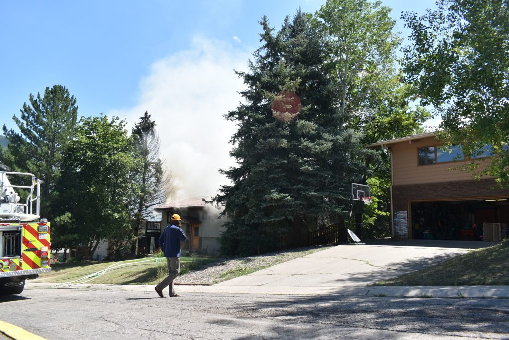 Ernie Mack watches as firefighters work to extinguish a fire at his neighbor's home Tuesday, Aug. 21.