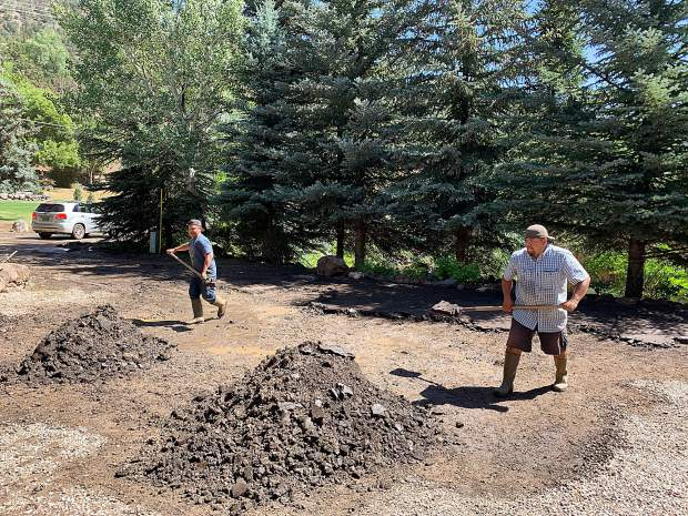Cousins Jayson (left) and Dorian Garcia were busy Monday morning shoveling mud and debris in the driveway and yard of a rental home on Sopris Avenue in Basalt, where floods and mud slides hit the area Sunday evening.