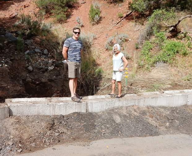 Keith McDougal and Geri Wright stand on a barrier at the intersection of Cedar Drive and Pinon in Basalt. Water from the Lake Christine Fire burn scar overwhelmed a culvert at that site and swamped the neighborhood.
