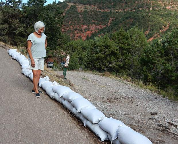 Geri Wright stands by the line of sandbags added to protect her home and property on Cedar Drive in Basalt from potential flooding. The town has ordered her and others to remove the bags because it contends they will make the flood potential worse.