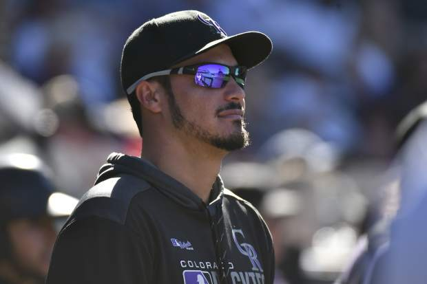 Colorado Rockies third baseman Nolan Arenado (28) looks on from the dugout during a baseball game against the Milwaukee Brewers, Sunday, Sept. 29, 2019, in Denver. (AP Photo/John Leyba)