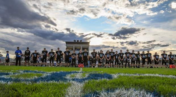 The Coal Ridge Titans line up along the sideline at the start of Friday night's game against the Olathe Pirates at Coal Ridge High School.