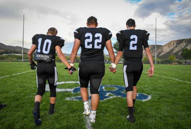 The Coal Ridge Titan captains make their way to the center of the field for the coin toss at the start of Friday night's game against the Olathe Pirates last Friday.