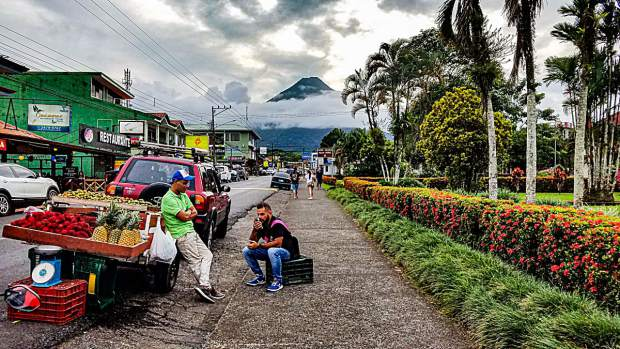 Produce vendors on the streets of La Fortuna, with Arenal Volcano in the background.