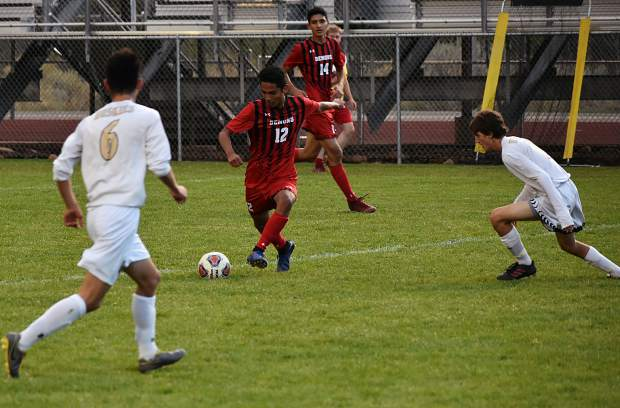 Glenwood senior Justin Garces looks for room Thursday against Battle Mountain as two Huskies defend in the first half.