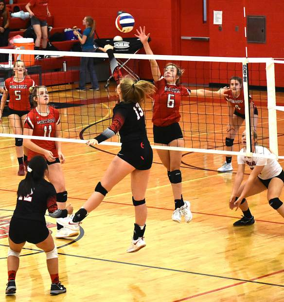 Glenwood Springs senior Emily Nilsson (13) tips a shot over the net as Montrose sophomore Taylor Foster defends Saturday inside Chavez-Spencer Gymnasium.