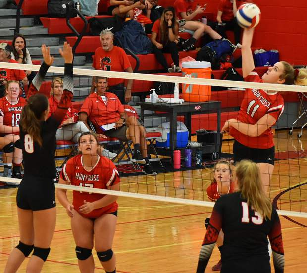 Montrose senior Madison Shatterly spikes the ball over the net as Glenwood sophomore Charlotte Olszewski (8) and senior Emily Nilsson (13) look on.