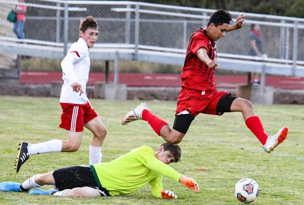 Glenwood Springs Demon German Alvarado jumps over the goalie in an attempt to score against the Montrose goalie in action at Stubler Memorial Field this season.