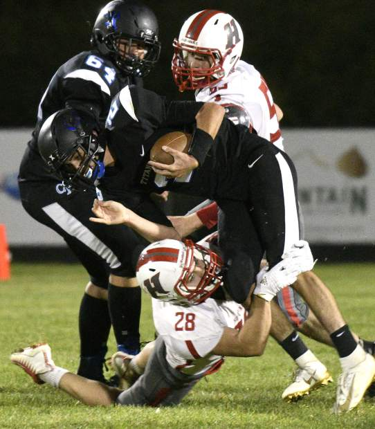 Coal Ridge's Karsen DuBois is tackled by Hotchkiss' Ian Aguleria as he tries to scramble for a first down late in the fourth quarter in New Castle. The Titans came up short on the play and the game losing to the Bulldogs 7-6 Friday.