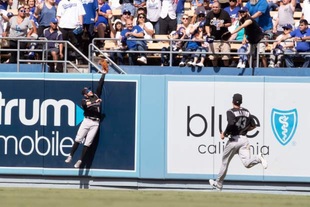 Colorado Rockies center fielder Garrett Hampson, left, tries to catch a home run by Los Angeles Dodgers' Hyun-Jin Ryu in the bottom of the fifth inning of a baseball game in Los Angeles, Sunday, Sept. 22, 2019. (AP Photo/Sam Gangwer )
