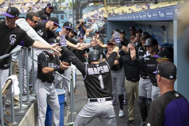 Colorado Rockies' Garrett Hampson is congratulated by teammates in their dugout after hitting a solo home run off Dodgers Hyun-Jin Ryu in the first inning inning of a baseball game in Los Angeles, Sunday, Sept. 22, 2019. (AP Photo/Sam Gangwer )