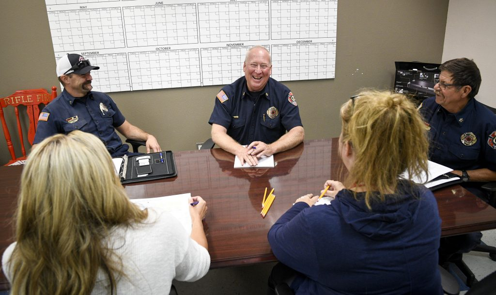 Colorado River Fire Rescue Fire Chief Randy Callahan enjoys a laugh with member of his adminstration staff, clockwise from bottom left, PJ Tillman, Leif Sacett, Orrin Moon Maria Pina during an afternoon meeting at Station 41 in Rifle.