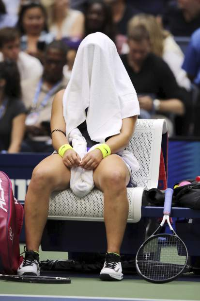 Bianca Andreescu, of Canada, sits with a towel over her head between games against Serena Williams, of the United States, during the women's singles final of the U.S. Open tennis championships Saturday, Sept. 7, 2019, in New York. (AP Photo/Charles Krupa)