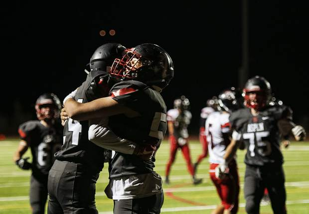 Aspen High School's Jonathon Woodrow (24), left, and Aiden Ledingham (56), right, hug after a touchdown was scored for the Skiers during the homecoming game against Grand Valley High School in Aspen on Friday, September 27, 2019. (Kelsey Brunner/The Aspen Times)
