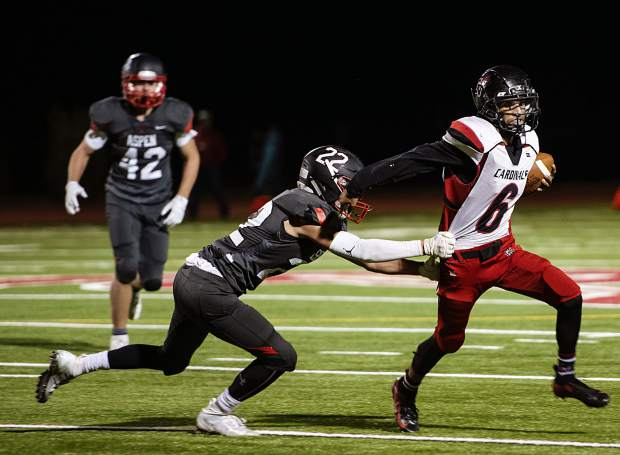 Aspen High School's Kip Royer (22), left, attempts to tackle Grand Valley's Hector Delacruz (6) during the homecoming game in Aspen on Friday, September 27, 2019. (Kelsey Brunner/The Aspen Times)