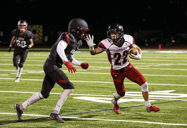 Grand Valley High School's Caleb Frink (22) fends off Aspen High School's Jack Seamans (6), left, during the homecoming game in Aspen on Friday, September 27, 2019. (Kelsey Brunner/The Aspen Times)