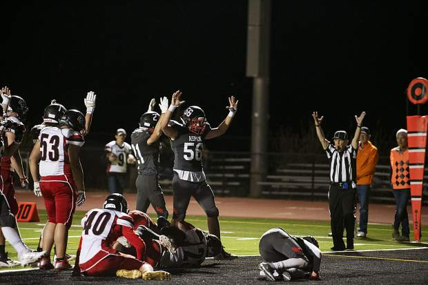 Aspen High School Skiers raise their hands to signal the touchdown scored by Jon Haisfield (12) during the homecoming game against Grand Valley High School in Aspen on Friday, September 27, 2019. (Kelsey Brunner/The Aspen Times)