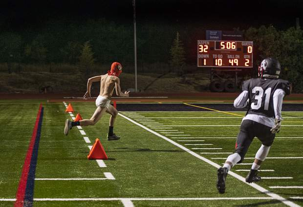 Aspen High School's Kiernon Smith, right, chases after a streaker during the 2nd quarter of the Homecoming game on Friday, September 27, 2019. (Kelsey Brunner/The Aspen Times)