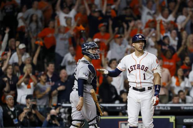 Houston Astros' Carlos Correa watches his walk-off home run against the New York Yankees during the 11th inning in Game 2 of baseball's American League Championship Series Sunday, Oct. 13, 2019, in Houston.. (AP Photo/Matt Slocum)