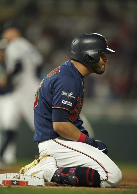 Minnesota Twins right fielder Eddie Rosario (20) stays for a minute on his knees after being tagged out at first base for the third out in the fifth inning in Game 3 of a baseball American League Division Series, Monday, Oct. 7, 2019, in Minneapolis. (Jeff Wheeler/Star Tribune via AP)