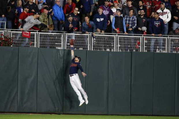 Minnesota Twins left fielder Jake Cave makes a leaping attempt at a home run hit by New York Yankees' Gleyber Torres during the second inning in Game 3 of a baseball American League Division Series, Monday, Oct. 7, 2019, in Minneapolis. (AP Photo/Bruce Kluckhohn)