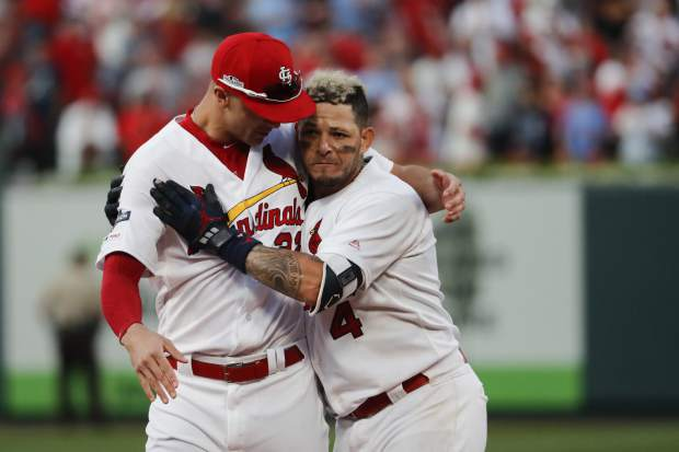 St. Louis Cardinals' Yadier Molina, right, celebrates with Jack Flaherty after hitting a sacrifice fly to score Kolten Wong and defeat the Atlanta Braves in Game 4 of a baseball National League Division Series, Monday, Oct. 7, 2019, in St. Louis. (AP Photo/Jeff Roberson)