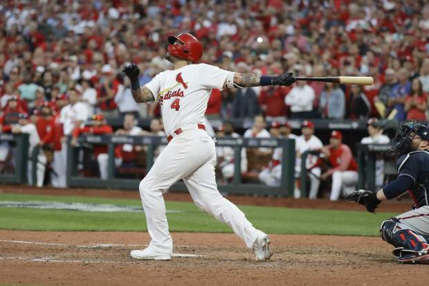 St. Louis Cardinals' Yadier Molina hits a sacrifice fly to score Kolten Wong for the winning run during the 10th inning in Game 4 of a baseball National League Division Series against the Atlanta Braves, Monday, Oct. 7, 2019, in St. Louis. (AP Photo, Charlie Riedel)