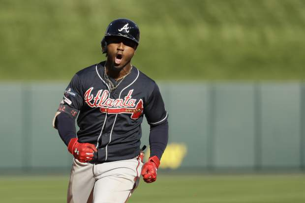 Atlanta Braves' Ozzie Albies celebrates after hitting a two-run home run during the fifth inning in Game 4 of a baseball National League Division Series against the St. Louis Cardinals, Monday, Oct. 7, 2019, in St. Louis. (AP Photo, Charlie Riedel)