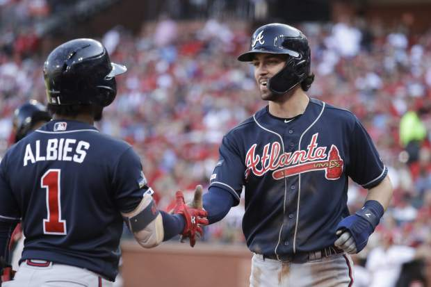 Atlanta Braves' Dansby Swanson, right, celebrates with Ozzie Albies (1) after scoring during the fifth inning in Game 4 of a baseball National League Division Series against the St. Louis Cardinals, Monday, Oct. 7, 2019, in St. Louis. (AP Photo/Charlie Riedel)