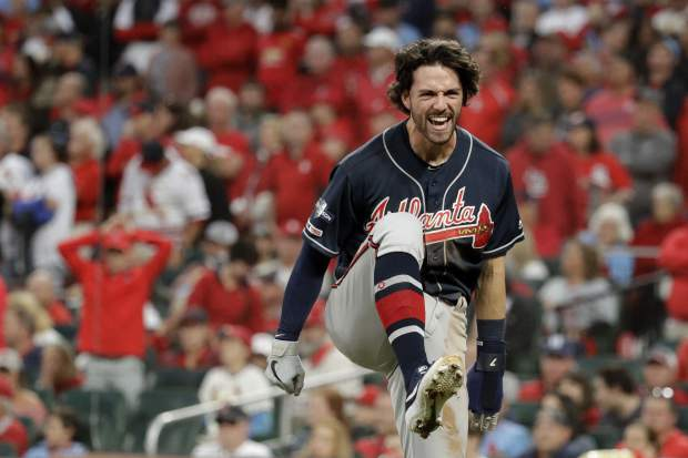 Atlanta Braves' Dansby Swanson celebrates after scoring during the ninth inning in Game 3 of a National League Division Series against the St. Louis Cardinals, Sunday, Oct. 6, 2019, in St. Louis. (AP Photo/Charlie Riedel)