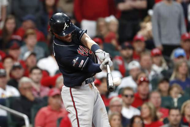Atlanta Braves' Dansby Swanson hits an RBI double during the ninth inning in Game 3 of the baseball team's National League Division Series against the St. Louis Cardinals on Sunday, Oct. 6, 2019, in St. Louis. (AP Photo/Jeff Roberson)