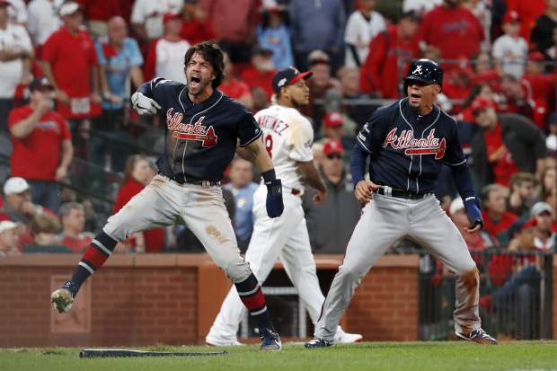 Atlanta Braves' Dansby Swanson, left, and Rafael Ortega, right, celebrate after scoring as St. Louis Cardinals relief pitcher Carlos Martinez (18) walks in the background during the ninth inning in Game 3 of a baseball National League Division Series on Sunday, Oct. 6, 2019, in St. Louis. (AP Photo/Jeff Roberson)