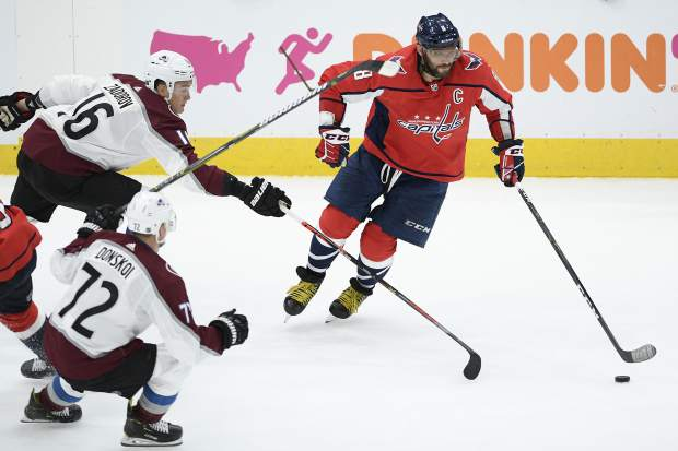 Washington Capitals left wing Alex Ovechkin (8), of Russia, skates with the puck against Colorado Avalanche defenseman Nikita Zadorov (16), also of Russia, and right wing Joonas Donskoi (72), of Finland, during the third period of an NHL hockey game, Monday, Oct. 14, 2019, in Washington. (AP Photo/Nick Wass)