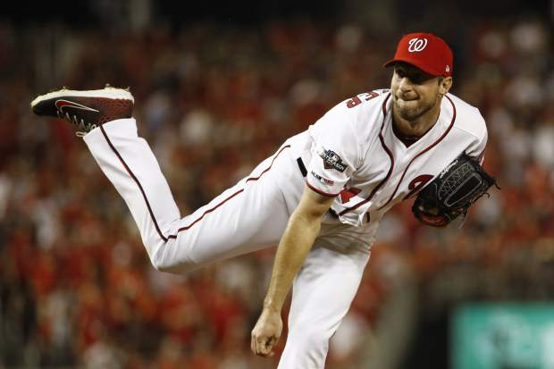 Washington Nationals starting pitcher Max Scherzer follows through on a pitch to the Milwaukee Brewers in the first inning of a National League wild card baseball game, Tuesday, Oct. 1, 2019, in Washington. (AP Photo/Patrick Semansky)