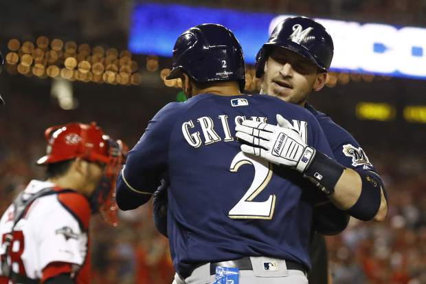 Milwaukee Brewers' Yasmani Grandal, right, celebrates with teammate Trent Grisham after batting Grisham in on a home run in the first inning of a National League wild card baseball game against the Washington Nationals, Tuesday, Oct. 1, 2019, in Washington. (AP Photo/Patrick Semansky)