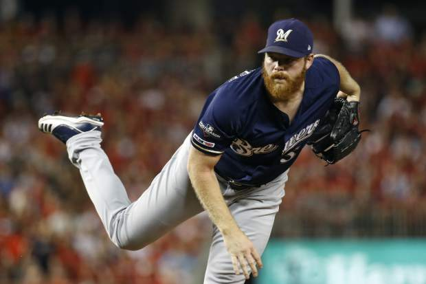 Milwaukee Brewers starting pitcher Brandon Woodruff follows through on a pitch to the Washington Nationals in the first inning of a National League wild card baseball game, Tuesday, Oct. 1, 2019, in Washington. (AP Photo/Patrick Semansky)