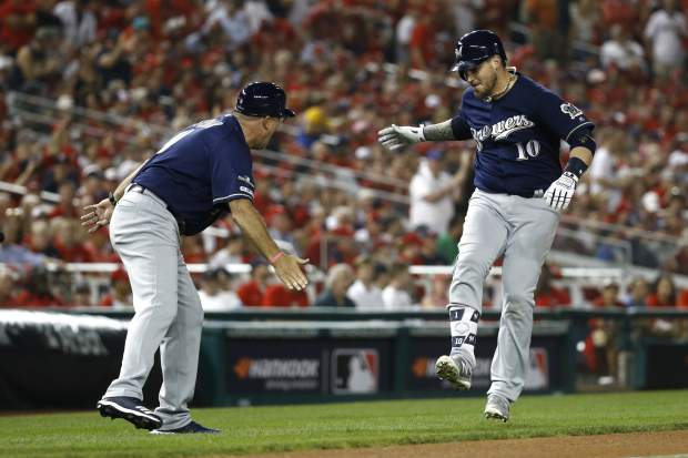 Milwaukee Brewers' Yasmani Grandal, right, rounds the bases past third base coach Ed Sedar after hitting a two-run home run in the first inning of a National League wild card baseball game against the Washington Nationals, Tuesday, Oct. 1, 2019, in Washington. (AP Photo/Patrick Semansky)